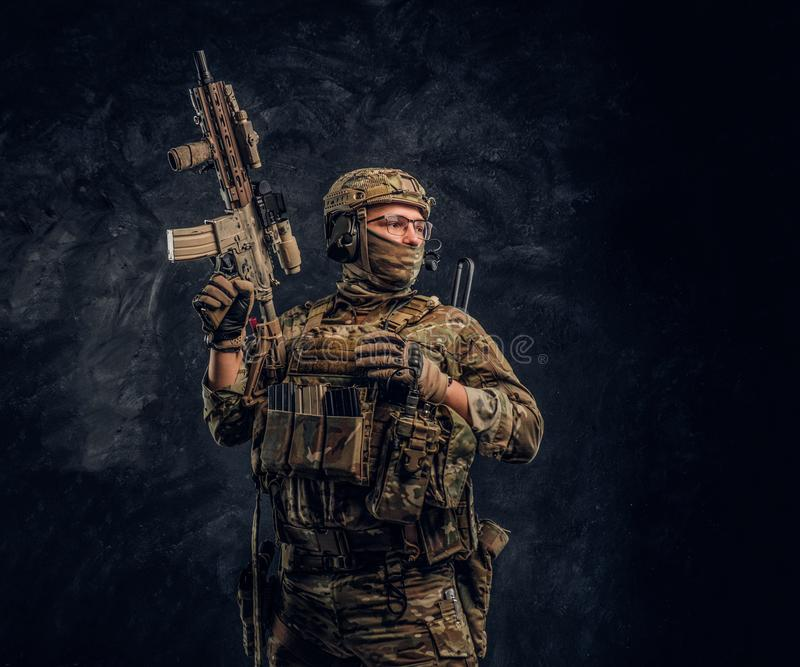 Fully equipped soldier in camouflage uniform holding an assault rifle. Studio photo against a dark wall royalty free stock images