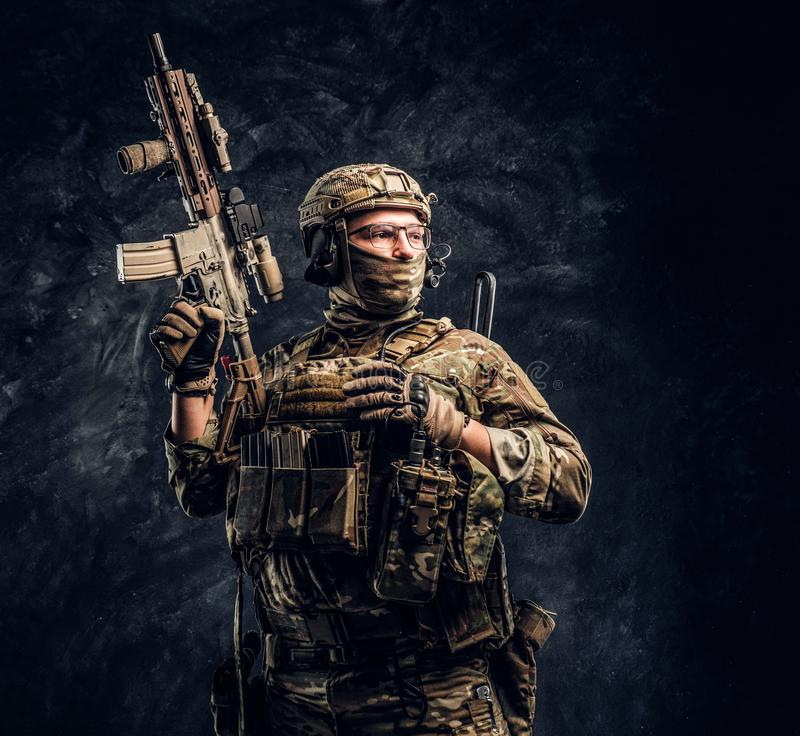 Fully equipped soldier in camouflage uniform holding an assault rifle. Studio photo against a dark wall stock photo