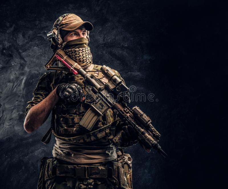 Fully equipped soldier in camouflage uniform holding an assault rifle. Studio photo against a dark wall royalty free stock photo