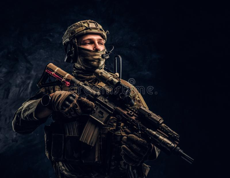 Fully equipped soldier in camouflage uniform holding an assault rifle. Studio photo against a dark wall royalty free stock image