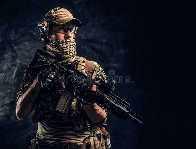 Fully equipped soldier in camouflage uniform holding an assault rifle. Studio photo against a dark wall stock images