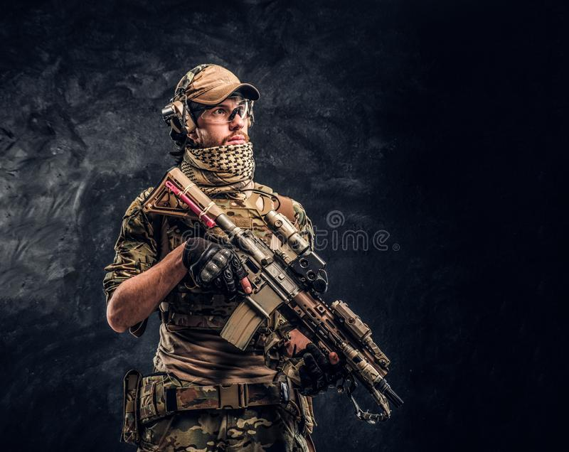 Fully equipped soldier in camouflage uniform holding an assault rifle. Studio photo against a dark wall stock photography