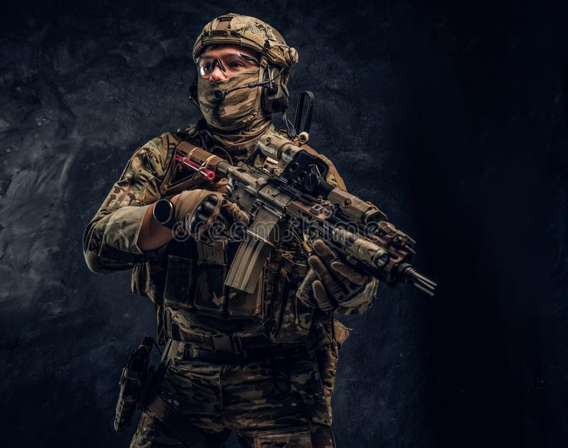 Fully equipped soldier in camouflage uniform holding an assault rifle. Studio photo against a dark wall royalty free stock photography