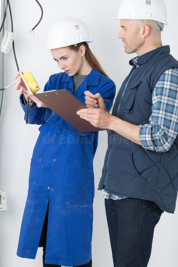 Fully-fledged electrician and female apprentice royalty free stock photos