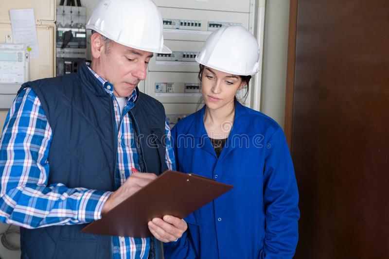 Fully-fledged electrician and female apprentice stock photography