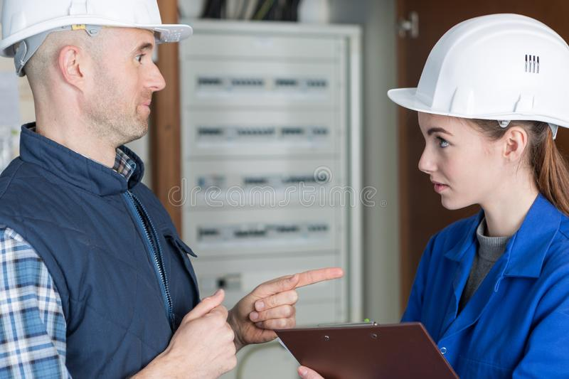 Fully-fledged electrician and female apprentice royalty free stock photography