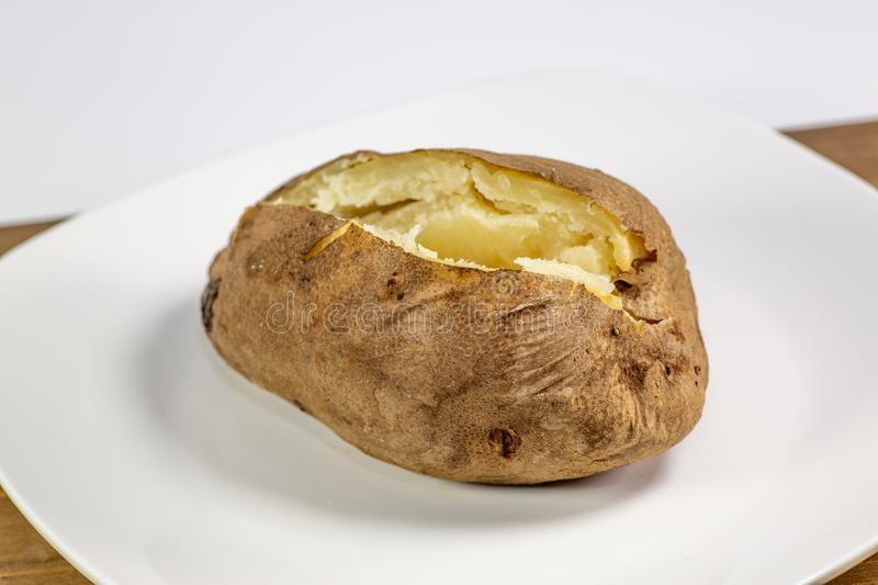 Fully loaded baked potato on a white plate on the kitchen table royalty free stock photography