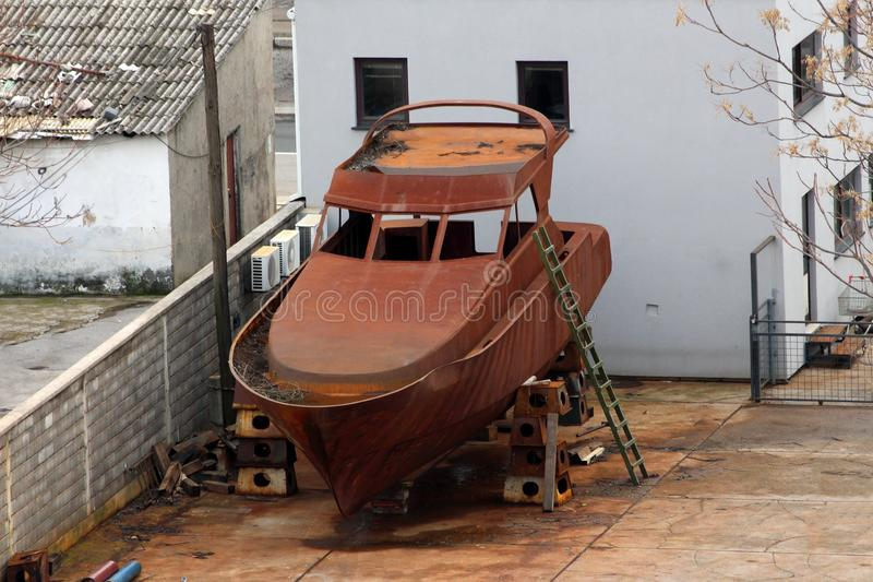 Fully rusted metal small sea boat put in backyard on strong supports to be restored to full glory with wooden ladder and family. Houses in background royalty free stock photos