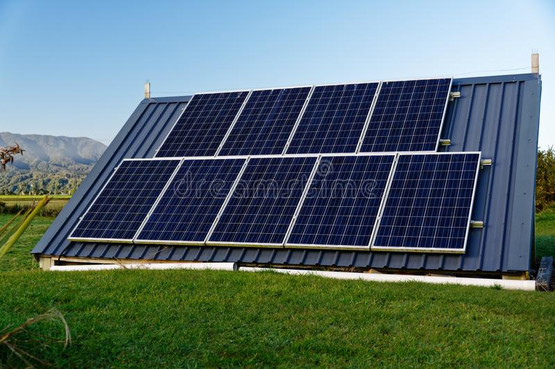 Fully self sufficient with an off grid, solar electricity system. Solar panels power an off grid electricity system to allow a house to be completely off the stock photos