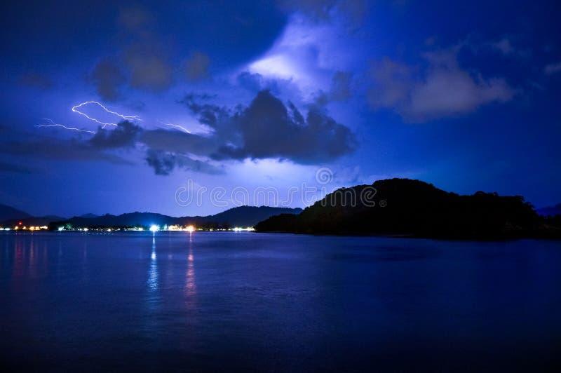 Fulmine sopra il mare calmo e una montagna fotografia stock