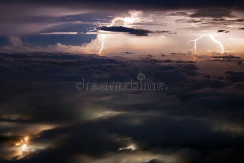 Fulmini multipli sopra la valle coperta di nuvole fotografia stock