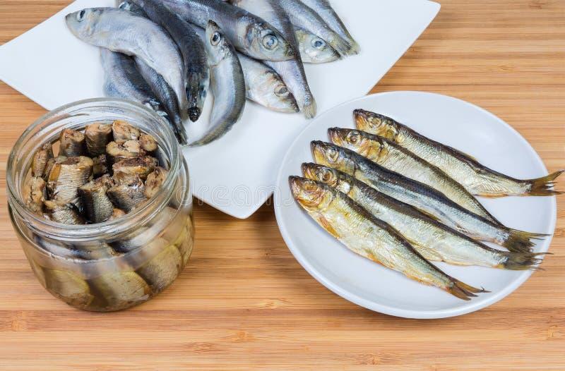 Fumé, préservé en huile de friture contre des harengs baltiques crus photographie stock libre de droits