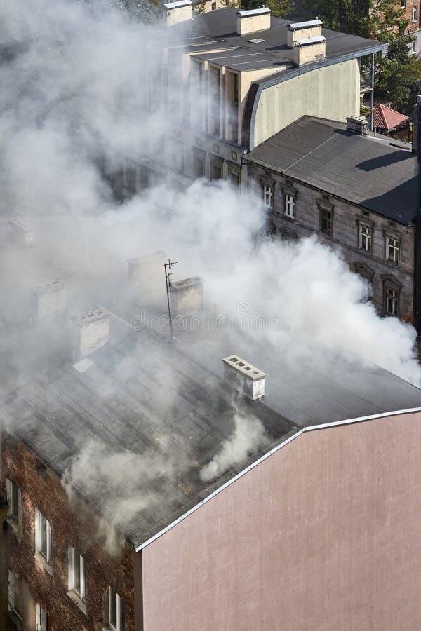 Fumée épaisse venant du toit d'un bâtiment sur le feu image stock