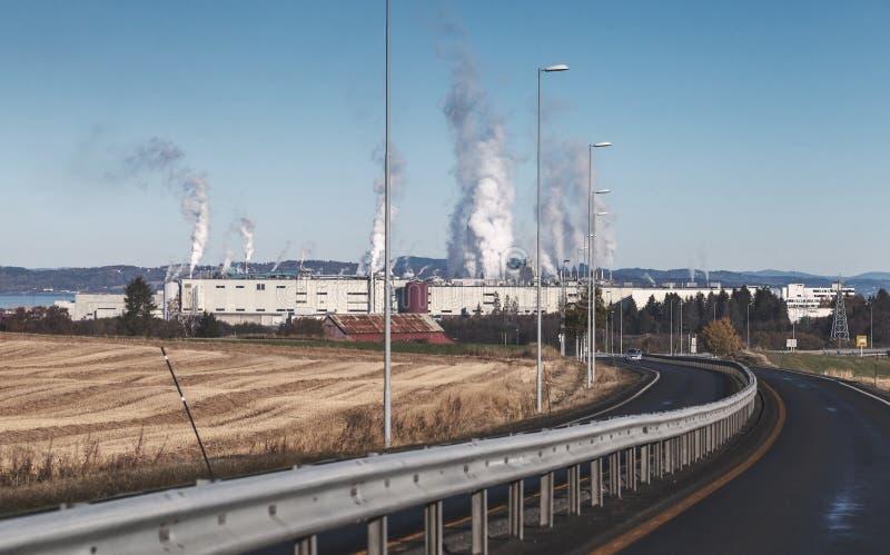 Fumée au-dessus d'usine de fabrique de pâte à papier Skogn, Norvège photos libres de droits