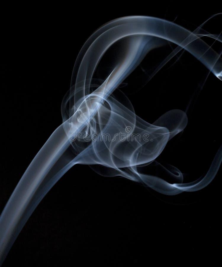 Fumée blanche sur le noir effectuant une boucle comme elle monte photos libres de droits