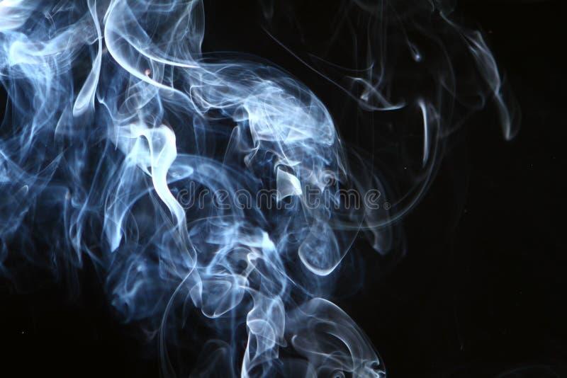 Fumée bleu-clair abstraite gentille sur le fond noir image libre de droits