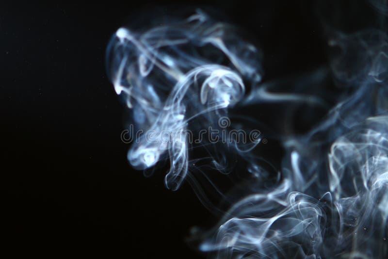 Fumée bleu-clair abstraite merveilleuse sur le fond foncé image libre de droits