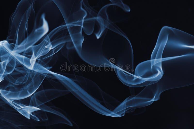 Fumée bleue sur le fond noir photographie stock libre de droits