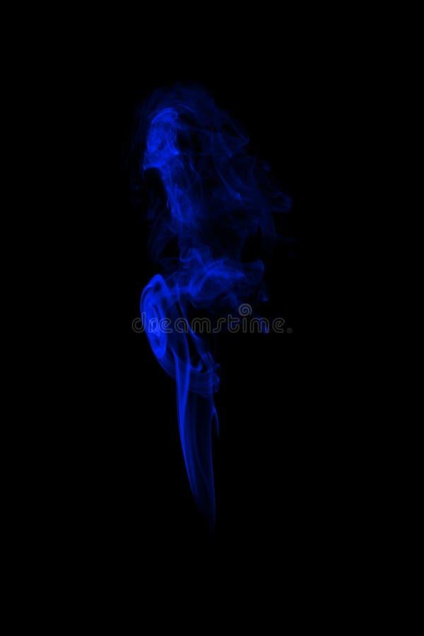 Fumée bleue sur le fond noir, image libre de droits