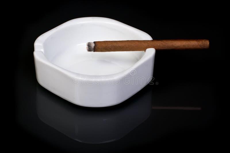 Fumée. Cendrier blanc avec le brun de cigarette sur un fond noir. photos stock