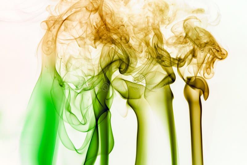 Fumée colorée de bâton d'incence d'isolement au fond blanc image libre de droits