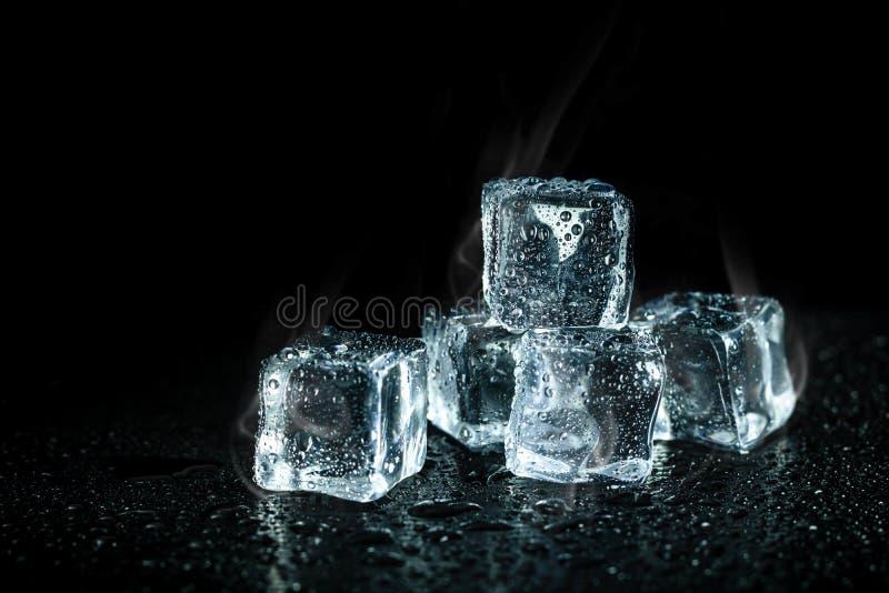 Fumée de glaçons et de refroidissement sur le fond foncé de table Blocs de glace avec les boissons froides photo libre de droits