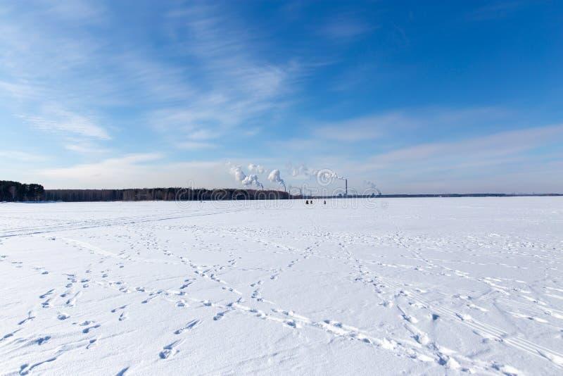 Fumée de l'usine près du lac congelé en hiver photo stock