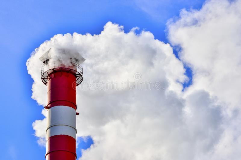 Fumée industrielle de cheminée sur le ciel bleu photographie stock libre de droits