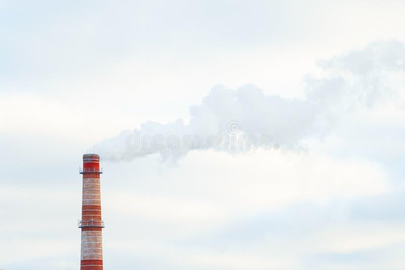 Fumée industrielle de la cheminée rouge sur le fond du ciel bleu image stock