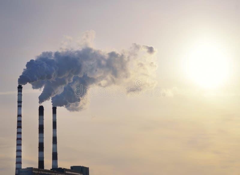 Fumée industrielle sur le coucher du soleil photo libre de droits