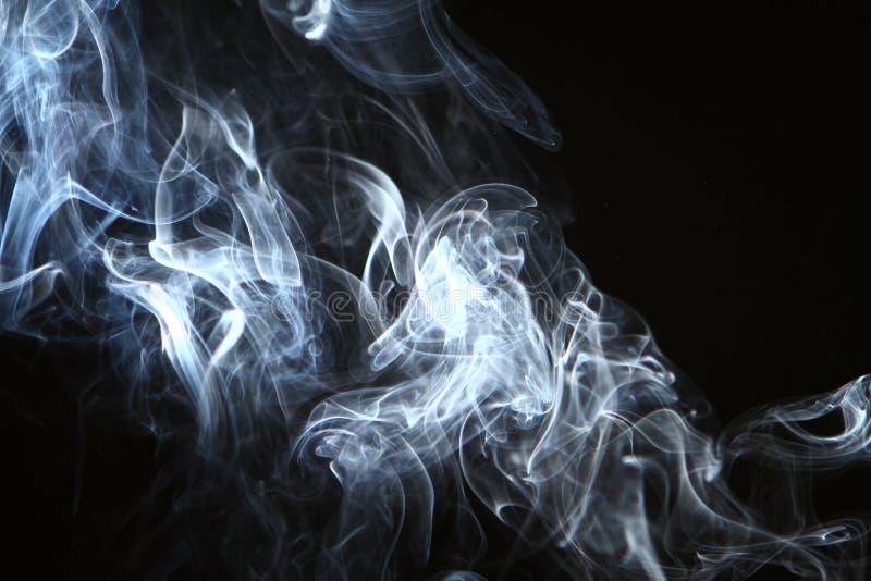 Fumée lumineuse rougeoyante de beau résumé sur le fond noir image stock