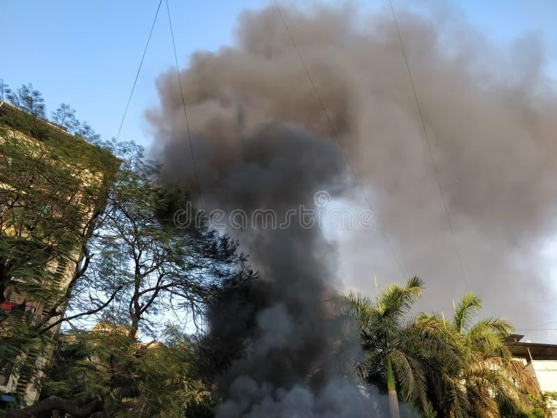 Fumée noire sortant d'un bâtiment sur le feu photos libres de droits