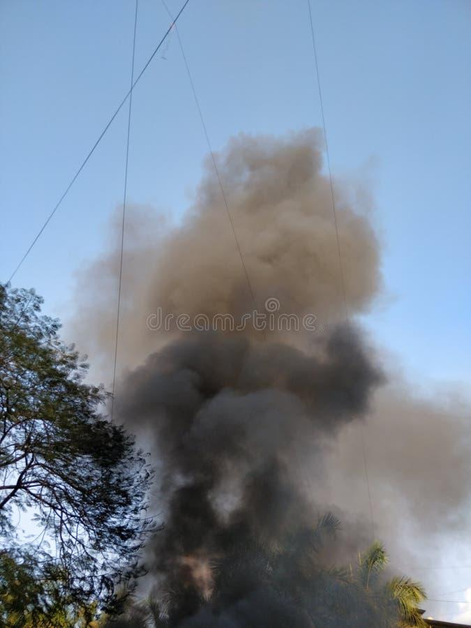 Fumée noire sortant d'un bâtiment sur le feu photographie stock