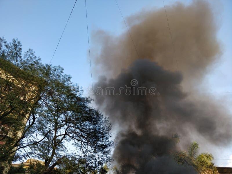 Fumée noire sortant d'un bâtiment sur le feu image stock