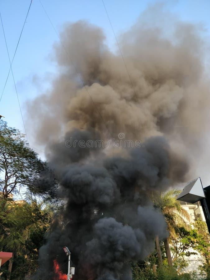 Fumée noire sortant d'un bâtiment sur le feu images stock