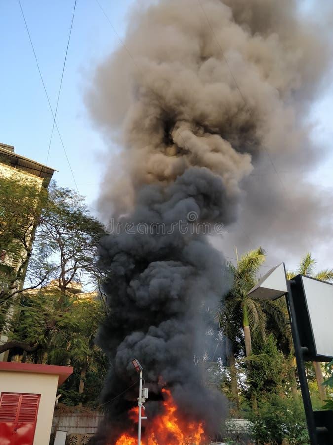 Fumée noire sortant d'un bâtiment sur le feu image libre de droits