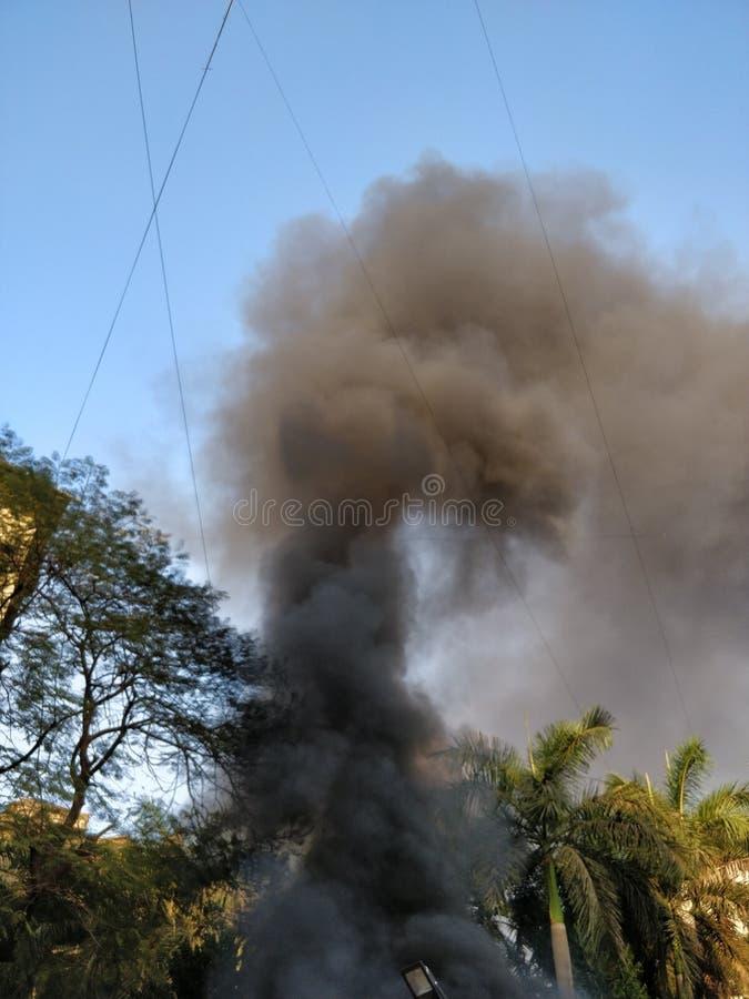 Fumée noire sortant d'un bâtiment sur le feu photo stock