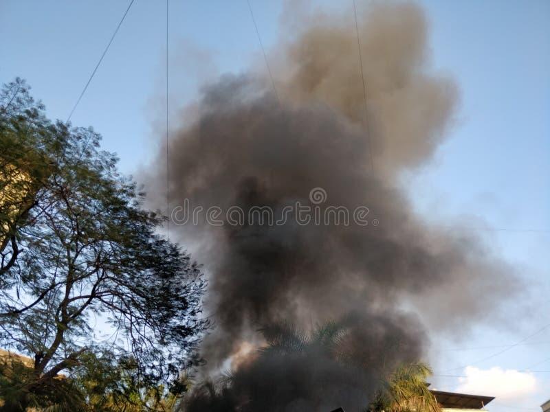 Fumée noire sortant d'un bâtiment sur le feu photos stock