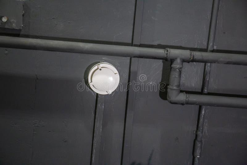 Fumée ou détecteur d'incendie sur la décellulation noire avec des tuyaux images libres de droits