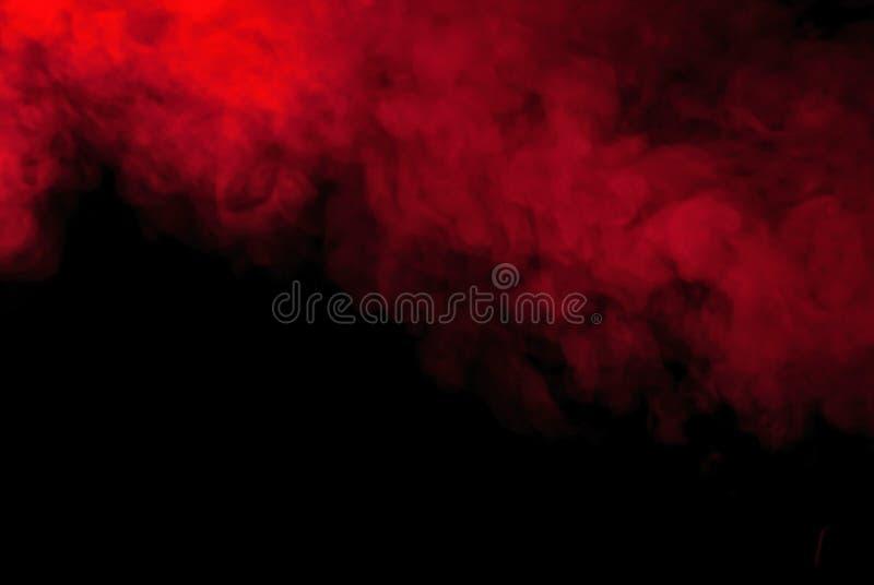 Fumée ou vapeur rouge sur un fond noir pour des papiers peints et des milieux image libre de droits