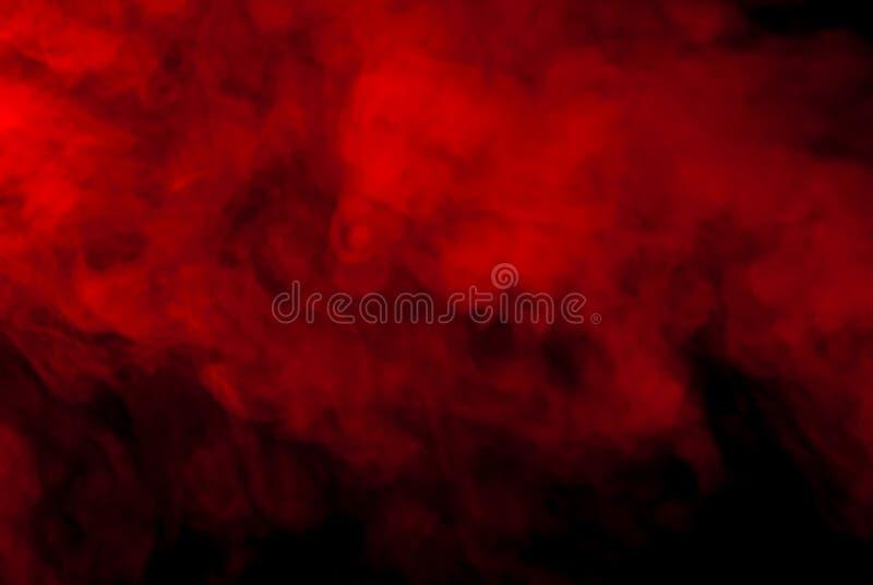 Fumée rouge sur un fond noir pour le papier peint photos stock