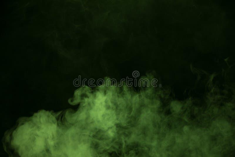 Fumée verte sur le fond noir photos stock