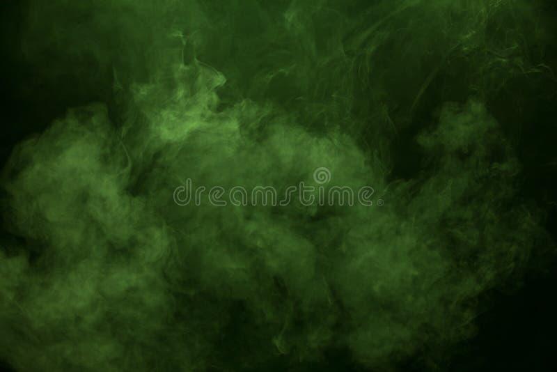 Fumée verte sur le fond noir image libre de droits