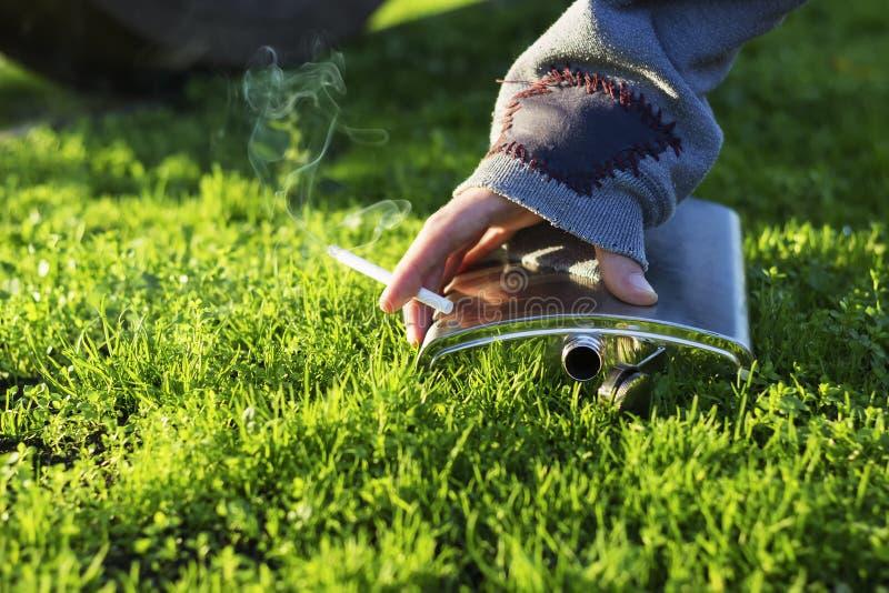 Fumador de cigarrillo que coge un frasco fotografía de archivo libre de regalías