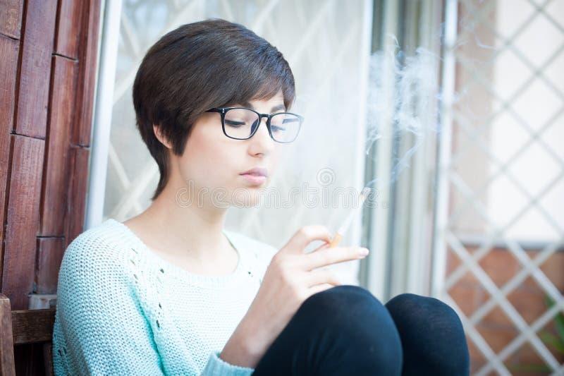 Fumando el tabaco de la mujer al aire libre, joven enviciado imagen de archivo