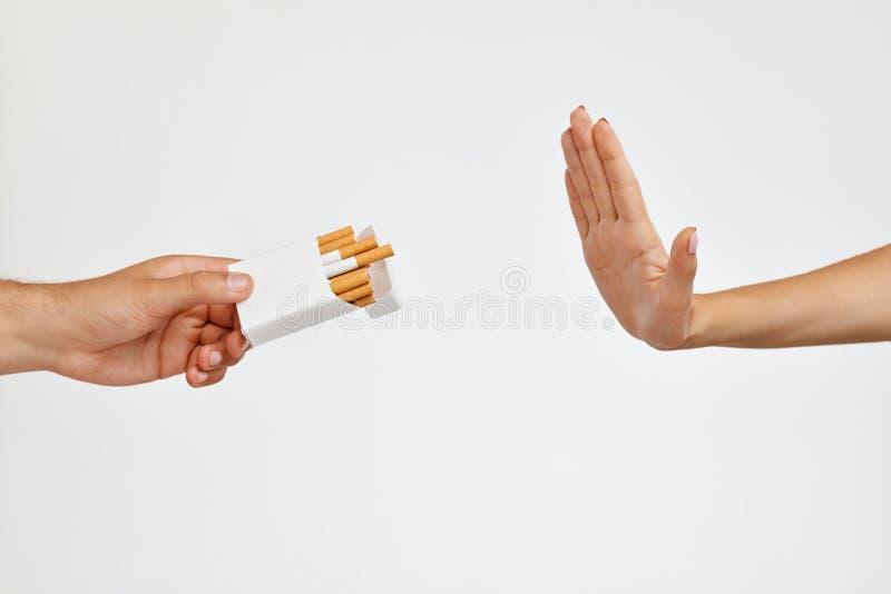 fumar Close up da mão da mulher que recusa tomar o cigarro imagens de stock royalty free