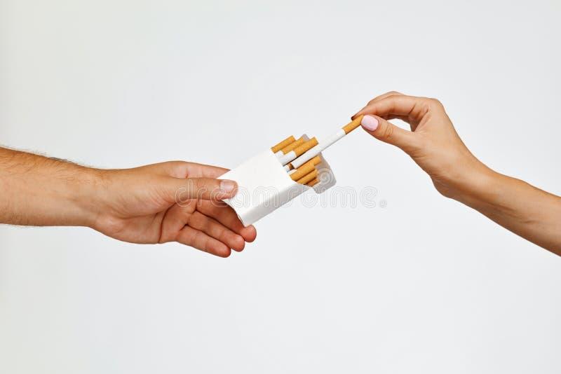 fumar Mão do close up que guarda o bloco dos cigarros, tomando o cigarro fotos de stock royalty free