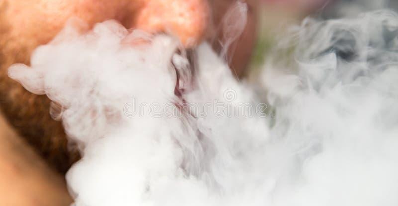 Fume de la nariz de un hombre de un cigarro fotografía de archivo libre de regalías