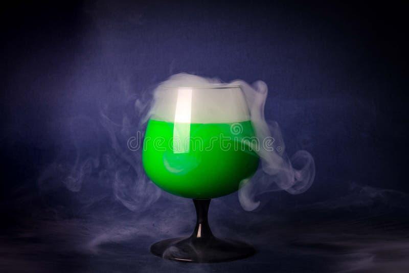 Fume en el vidrio de cóctel en un fondo negro Fondo de la poción de la bruja para Halloween Bebida inusual de la barra imagenes de archivo