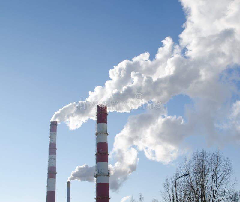 Fume o céu azul do calor das chaminés da fábrica da indústria da elevação fotografia de stock